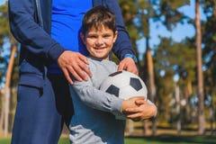 Niño feliz con la bola cerca del padre Imagen de archivo
