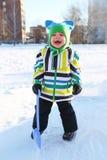 Niño feliz con la pala en invierno al aire libre Foto de archivo libre de regalías