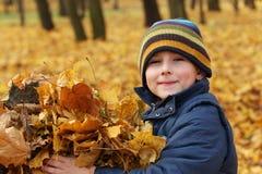 Niño feliz con las hojas de otoño Imagen de archivo libre de regalías