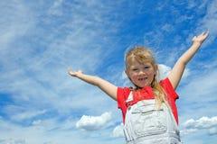 Niño feliz con las manos en el cielo azul grande. Imagen de archivo libre de regalías