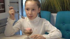 Niño feliz con las pecas en su cara que se sienta en un café, comiendo el helado y hablar Primer, alto detalle almacen de metraje de vídeo