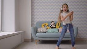 Niño feliz con los auriculares y smartphone que baila y que escucha la música en casa metrajes