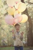 Niño feliz con los globos coloridos en la celebración Imagen de archivo libre de regalías