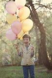 Niño feliz con los globos coloridos en la celebración Imagenes de archivo
