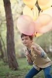 Niño feliz con los globos coloridos en la celebración Imágenes de archivo libres de regalías