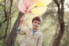 Niño feliz con los globos coloridos en la celebración Fotos de archivo