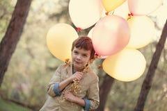 Niño feliz con los globos coloridos en la celebración Fotos de archivo libres de regalías