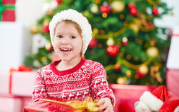 Niño feliz con los regalos de la Navidad cerca de un árbol de navidad Imágenes de archivo libres de regalías
