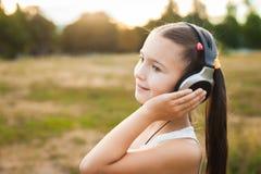 Niño feliz con música que escucha de los auriculares Fotos de archivo
