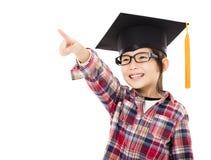 Niño feliz de la escuela en casquillo de la graduación con señalar gesto Foto de archivo