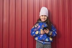 Niño feliz de la muchacha con smartphone en manos en un fondo rojo en la calle Vestido en una chaqueta azul y una sonrisa imagen de archivo