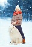 Niño feliz de la Navidad que camina con el perro blanco del samoyedo en nieve en día de invierno Imagen de archivo libre de regalías