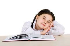 Niño feliz de la niña con un libro en el fondo blanco Fotografía de archivo