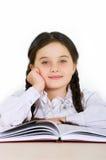 Niño feliz de la niña con un libro en un fondo blanco Foto de archivo libre de regalías
