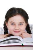 Niño feliz de la niña del retrato del primer con un libro en un blanco Fotos de archivo libres de regalías