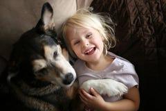 Niño feliz, de risa de la niña que abraza el perro casero en el sofá imagen de archivo