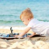 Niño feliz del bebé con tecnología en la playa Imagen de archivo