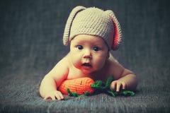 Niño feliz del bebé en traje un conejito del conejo con la zanahoria en un gris Imagenes de archivo