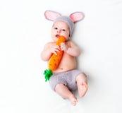 Niño feliz del bebé en traje un conejito del conejo con la zanahoria en una pizca Fotografía de archivo libre de regalías