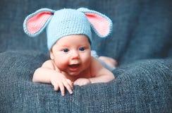 Niño feliz del bebé en traje un conejito del conejo en un gris Foto de archivo libre de regalías