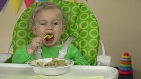 Niño feliz del bebé que se sienta en silla con una cuchara y que come la comida deliciosa del niño almacen de metraje de vídeo