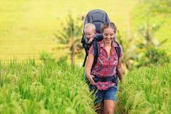 Niño feliz del control de la mujer en portador de bebé de la mochila imagenes de archivo