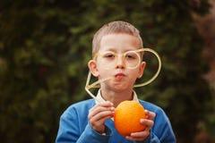 Niño feliz del retrato que bebe el zumo de naranja en día de verano foto de archivo libre de regalías