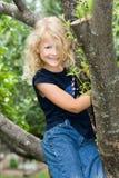 Niño feliz en árbol. Imagen de archivo