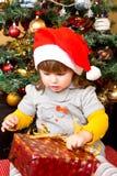 Niño feliz en caja de regalo de la Navidad de la abertura del sombrero de Papá Noel Imagen de archivo libre de regalías