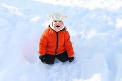 Niño feliz en chaqueta anaranjada en invierno Imagen de archivo