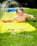 Niño feliz en diapositiva de agua Imagen de archivo libre de regalías