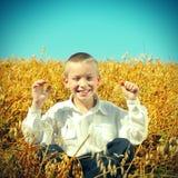 Niño feliz en el campo de trigo Imágenes de archivo libres de regalías