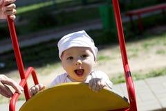 Niño feliz en el oscilación imagenes de archivo