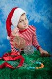 Niño feliz en el sombrero de Papá Noel en fondo azul Imagenes de archivo