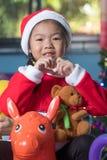 Niño feliz en el sombrero de santa con un regalo cerca del árbol de navidad, Ch Imagen de archivo