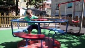 Niño feliz en el tiovivo en playgroung metrajes