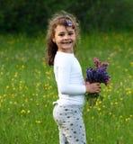 Niño feliz en flores de la primavera Foto de archivo libre de regalías