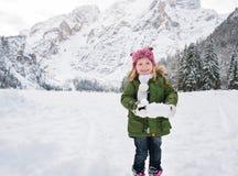 Niño feliz en la capa verde que juega con nieve al aire libre Fotografía de archivo