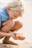 Niño feliz en la playa que recoge cáscaras del mar Foto de archivo