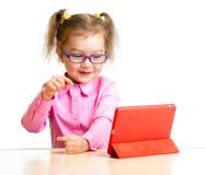 Niño feliz en los vidrios que miran la mini pantalla de la PC de la tableta del ipad Imágenes de archivo libres de regalías