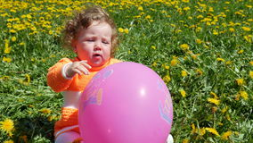 Niño feliz en un claro de la primavera en dientes de león con su familia almacen de metraje de vídeo