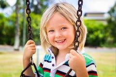 Niño feliz en un oscilación en tierra del juego imagenes de archivo