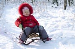 Niño feliz en un paisaje del invierno del trineo, espacio libre Foto de archivo