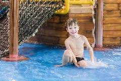 Niño feliz en una pequeña piscina que vadea imagenes de archivo