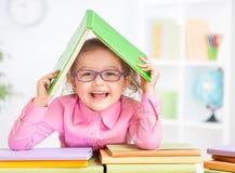 Niño feliz en vidrios debajo del tejado hecho del libro imagen de archivo libre de regalías