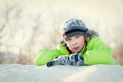 Niño feliz en winterwear que sonríe mientras que juega en nieve acumulada por la ventisca Imagen de archivo