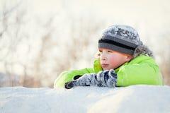 Niño feliz en winterwear que sonríe mientras que juega en nieve acumulada por la ventisca Imagen de archivo libre de regalías