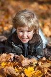 Niño feliz entre las hojas de otoño Fotos de archivo libres de regalías