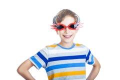 Niño feliz hermoso en la camiseta colorida que lleva las gafas de sol elegantes Fotografía de archivo
