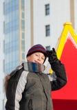 Niño feliz lindo que lleva la chaqueta caliente del invierno y un sombrero que juega al aire libre Imagen de archivo
